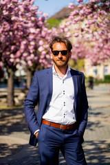 Junger Mann im Anzug mit Sonnenbrille vor Kirschblüten