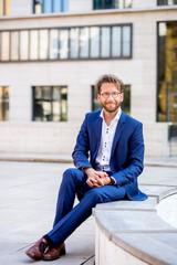 Junger Mann im Anzug sitzt lächelnd vor einem Bürogebäude