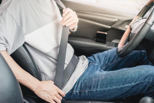 a male driver is  wearing seatbelt