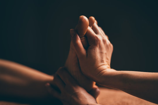 Professional foot massage close up. Authentic shot of luxury spa treatment. Charming light. Shallow depth of field. Stylized and colored. Copy space