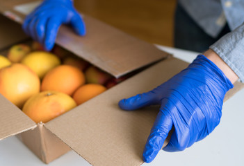 Volunteer in protective medical gloves putting fruits In donation box.