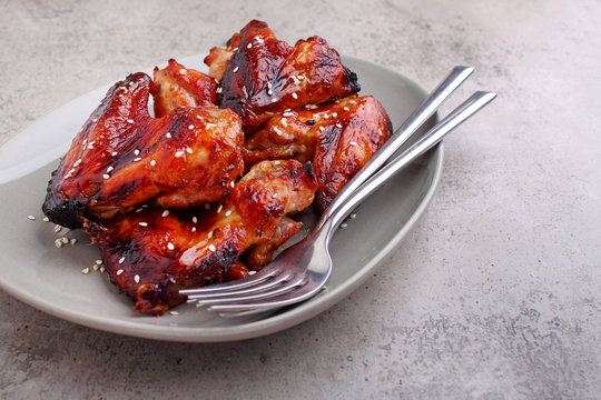 Grilled chicken wings in soy sauce decorated with sezame in a plate on a concrete background