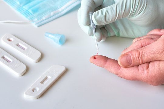 Rapid COVID-19 test for detection of specific antibodies IgM and IgG to novel corona virus SARS-CoV-2 causing Covid-19 illness. Medic or doctor in protective gloves collects blood from patient finger