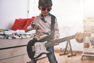 boy play electric guitar and learns