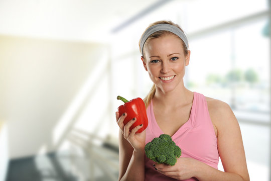 Young beautiful woman holding a brocolli and a pepper