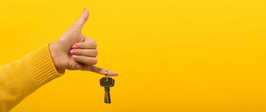 hand holding house keys over yellow background, panoramic mock-up