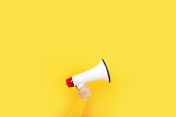 megaphone in hand on a yellow background, advertising concept