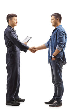 Young mechanic shaking hands with a casual man