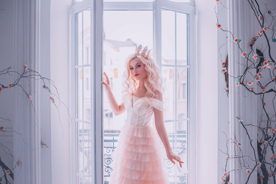Beautiful woman queen gently touches open window hand. Smiling face glamour fashion model. Girl Princess blond long wavy curl hair Luxury pink dress gold crown. Backdrop white room interior black tree