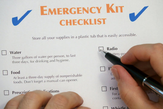 An emergency kit checklist is shown up close, just before being checkmarked by hand with an ink pen.
