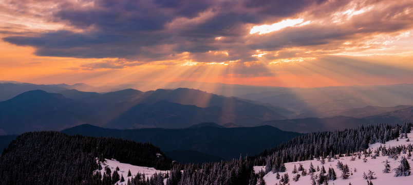 sunbeams through the clouds at sunrise on the snowy mountain