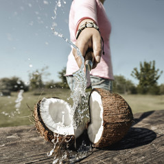 Person zerteilt Kokosnuss