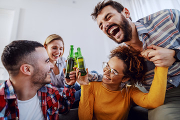 Group of cheerful friends having fun at home, toasting with beer and laughing.