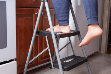 A view of a person and their feet on a two level step ladder in a kitchen setting. One foot is hanging off. - fototapety na wymiar
