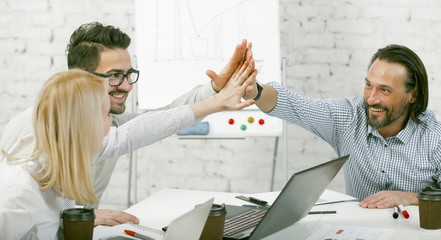 High-five gesture. Colleagues joined their hands in a sign of unity sitting at the desk. Happy...