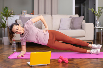 Beautiful sporty cheerful woman is doing side plank exercise
