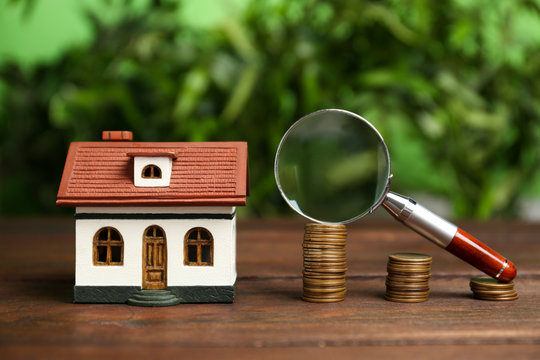 House model, coins and magnifying glass on wooden table against blurred background. Search concept