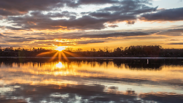 The sun bursts through the clouds at dawn on Blue Marsh Lake in Berks County, PA