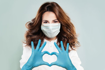 Optimistic doctor woman in protective mask making heart. Help, support, healthy lifestyle,...