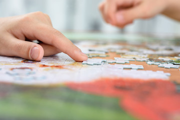 Close-up of children's hands collecting jigsaw puzzles