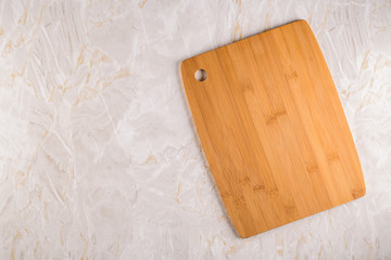 Wooden cutting board on a gray marble background