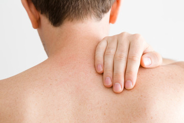 Young man massaging his shoulder with hand. Pain from strain of sedentary long work, overwork and incorrect posture. Inactive lifestyle. Back view. Close up.