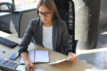 Attractive business woman holding documents and looking at them while sitting at the desk in office