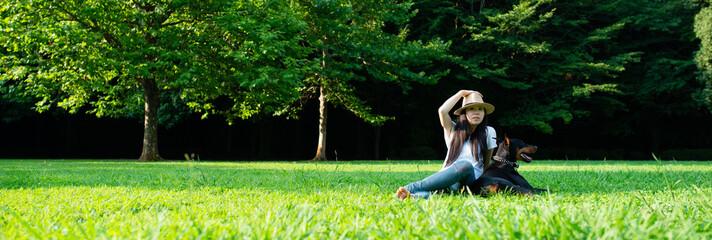 芝生で寛ぐ日本人女性とドーベルマン