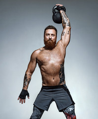 Muscular man training with kettlebell. Photo of man with naked torso on grey background. Strength and motivation