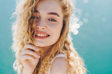 curly blonde smiling broadly with a gentle gaze of blue eyes against the background of sparkling water