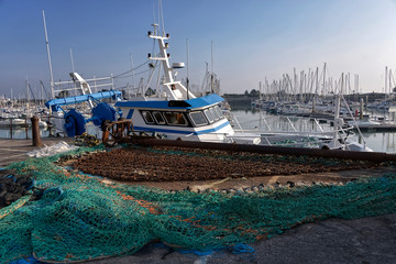 Fishing boat and fishing net in the port of Saint-Vaast-la-Hougue, a commune in the peninsula of Cotentin in the Manche department in Lower Normandy in north-western France