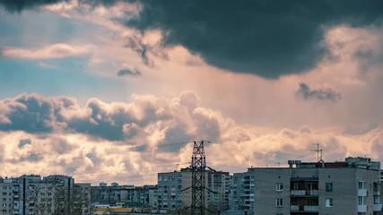 Fotobehang - Rainy storm clouds moving over city skyline sky background. Zoom in on power line pylon. Timelapse, 4K UHD.