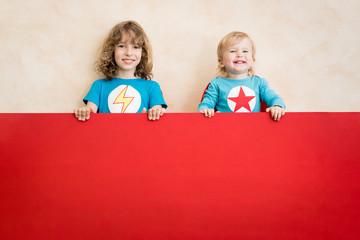 Superheroes children holding red banner blank