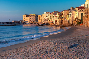 Fotomurales - Beautiful view of empty sunny sand beach and old town of coastal city Cefalu at sunset, Sicily, Italy