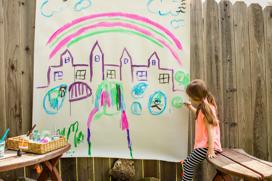 A young girl painting a castle on a large piece of paper outside in the backyard.