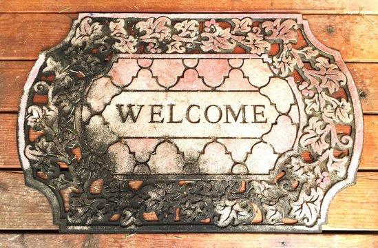 Directly Above View Of Welcome Door Mat On Wooden Floor