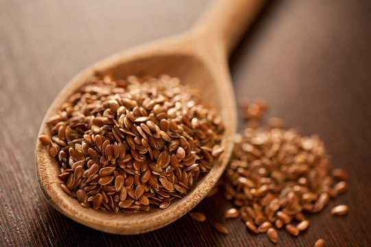 Close-up Of Brown Flaxseeds On Spoon At Table