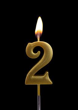 Burning birthday golden candle isolated on black background, number 2