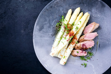 Fried Iberian pork fillet sliced with blanched white asparagus and herbs with spice as closeup on a modern design plate with copy space left