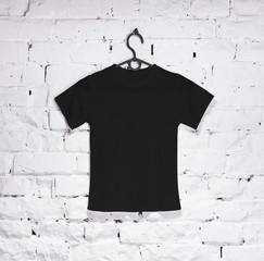 Black t-shirt for kids on hanger on a white brick wall