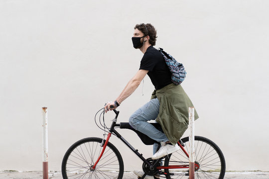 Young adult cyclist man walking in the city riding his bicycle. Hipster guy wearing a black safety mask over a bike against a white wall. Urban shot during coronavirus pandemic epidemics.