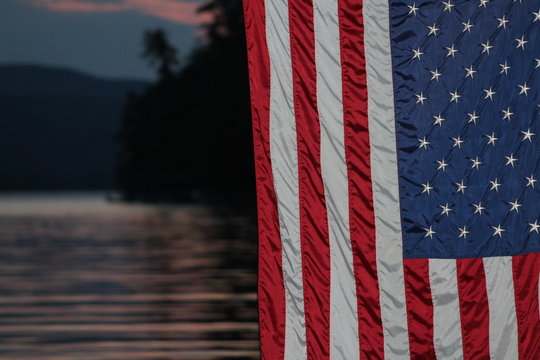 Close-up Of American Flag Against Lake
