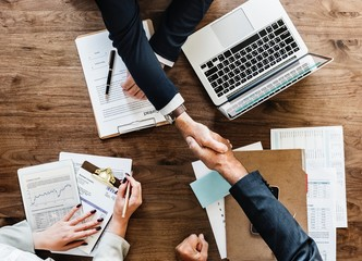 Midsection Of Business People Shaking Hands On Table