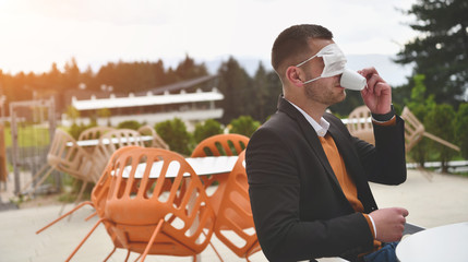 funny man in restaurant drinking coffee wearing face mask