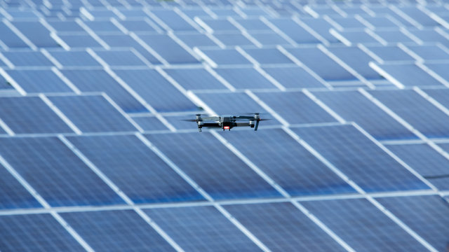 Flying Drone inspection explores the work of solar cell panel with strong sun and sky in solar farm