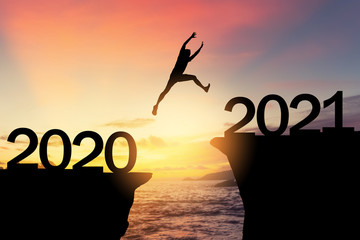Silhouette man jumping between cliff with number 2020 to 2021 at tropical sunset beach. Freedom...