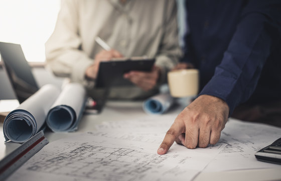 Architect working on blueprint. Architects workplace - architectural project, blueprints, ruler, calculator, laptop and divider compass. Construction concept. Blue print is fake only for stock photo.
