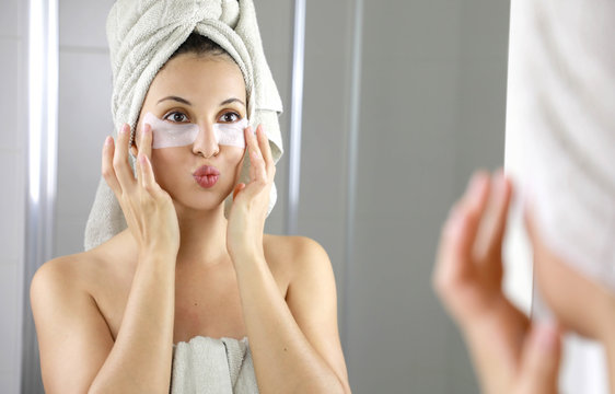 Beautiful woman applying anti-fatigue under-eye mask kissing herself in the mirror in the bathroom. Skin care girl touch patches of fabric mask under eyes to reduce eye bags.