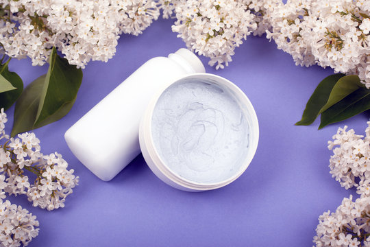 white bottles with cosmetics for skin care with white lilac flowers on the violet background close-up. beauty, wrinkle prevention