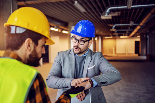 Serious nervous supervisor arguing with his worker and pointing at wristwatch. Work must be done on time with no excuses. Building in construction process interior.